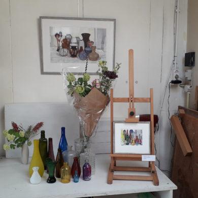 Op het atelier, stillevenhoekje met bloemen en 2 werken. Boven: Vazenland, Marijke de Jong, gemengde technieken. Onder: Glazenvazenland, Marijke de Jong, collage